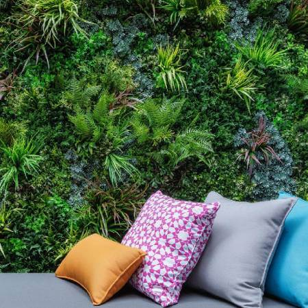 Couch with pillows in front of a SYNLawn vistafolia artificial living wall